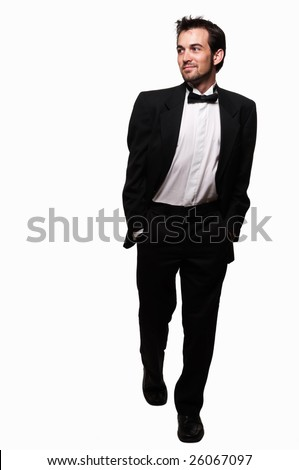 Full body of an attractive young brunette man with a beard wearing a black tuxedo stepping