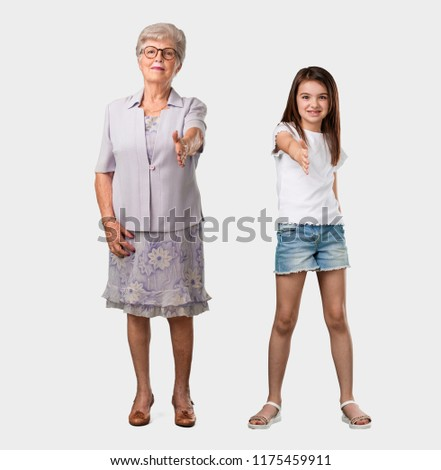 Free photos a hand reaching out to someone avopix full body of an elderly lady and her granddaughter reaching out to greet someone or gesturing m4hsunfo