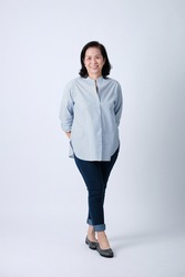 Full body of an happy asian old woman in light blue shirt and dark blue pants standing in studio white background.