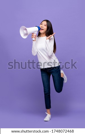 Full body of  beautiful Asian woman announcing on magaphone isolated on purple background