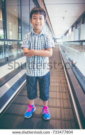 Full body of happy asian child standing on electric speedwalk at modern airport. Handsome boy smiling and looking at camera. Travel on vacation. Vintage film filter effect. #733477804