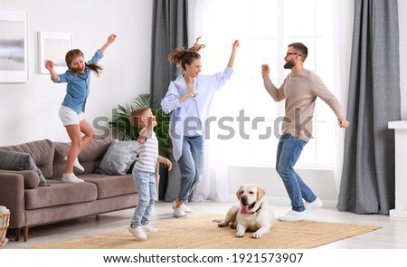 Full body of happy energetic family: parents and kids having fun and dancing while cute tired dog resting on carpet during weekend at home Stockfoto ©