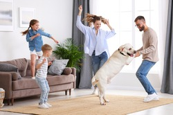 Full body of happy playful family: parents and little kids with cute purebred Labrador retriever dog having fun and dancing together in living room at home