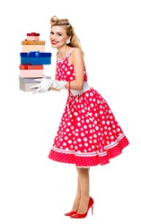 Full body of happy woman in pin-up style red dress in polka dot and white gloves, holding gift boxes, isolated on white background. Caucasian blond model posing in retro fashion and vintage shoot.