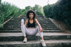 Full body of slim black female athlete with bottle of water in sport leggings and sneakers relaxing on stairs against green trees