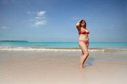 Full body of smiling overweight woman covering face from sunlight while standing on sandy beach near waving sea