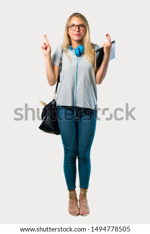 Full body of Student girl with glasses with fingers crossing and wishing the best. Making a wish. on grey background