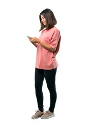 Full body of  Young girl with pink shirt sending a message or email with the mobile. Ideal for use in architectural designs