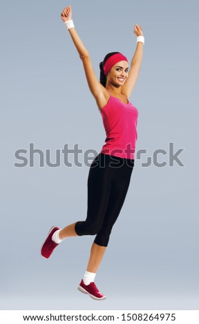 Full body of young happy african american girl in red sportswear doing fitness exercise, isolated against grey color studio background. Woman fitness and workout concept picture.