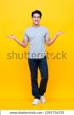 Full body of young happy handsome Asian man raising his hands with open palms gesture studio shot isolated on colorful yellow background