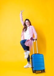 Full body photo emotional happy girl in trendy stylish clothes,sunglasses, holding ticket and passport,blue suitcase enjoying rising hand showing peace sign with two fingers isolated yellow
