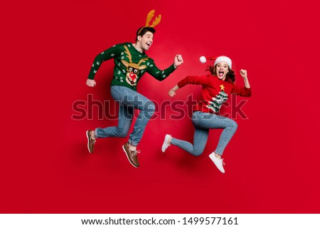 Full body photo of amazed jumping couple excited by x-mas prices hurry shopping wear ugly ornament jumpers isolated red color background