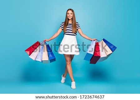 Full body photo of charming funny lady tourist walk shopping center carry many packs good mood best weekend wear white striped t-shirt skirt shoes isolated blue background