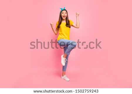 Full body photo of cheerful girl raising fists screaming wow omg yeah wearing yellow t-shirt isolated over pink background