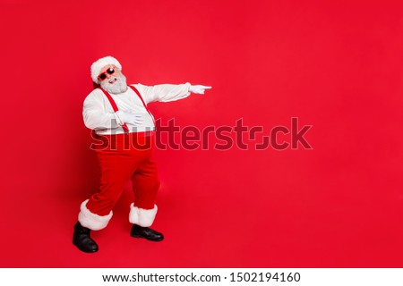 Full body photo of comic bully fat overweight santa claus with funny big belly point at loser laugh wear overalls suspenders have stylish trendy style eyewear isolated over red background