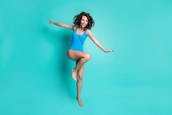 Full body photo of comical cheerful playful model young girl lady dance exercise high knee jump activities beach pool aerobics hands wings wear blue swimsuit isolated teal color background