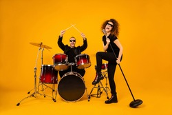 Full body photo of cool rock group handsome guy play drum instruments crazy girl sing old fashion mic concert popular band wear trendy rocker leather outfit isolated yellow background