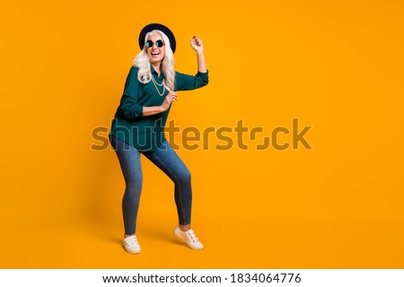 Full body photo of crazy granny lady music lover senior party luxury cool look dance youth moves wear green shirt sun specs necklace retro cap shoes isolated yellow color background