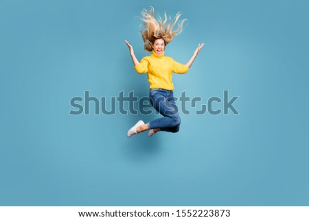 Full body photo of crazy lady jumping high enjoy autumn breeze hairdo flying cheerful person wear knitted yellow pullover jeans isolated blue color background