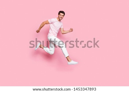 Full body photo of crazy person with toothy beaming smiling running isolated over pink background