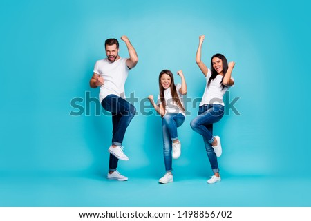 Full body photo of daddy mommy and small lady raising fists air rejoicing wear casual outfit isolated blue background