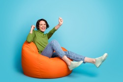 Full body photo of ecstatic girl enjoy rejoice lucky triumph win raise fists scream sit bean chair wear sweater isolated over blue color background