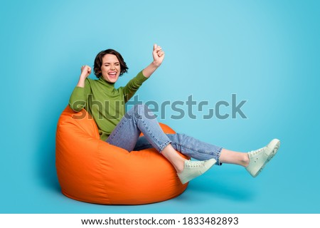 Full body photo of ecstatic girl enjoy rejoice lucky triumph win raise fists scream sit bean chair wear sweater isolated over blue color background Foto stock ©