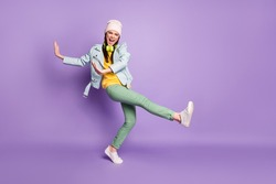 Full body photo of funky attractive lady street stylish clothes good mood dancing youngster moves raise hands leg high wear casual hat jacket pants shoes isolated purple color background