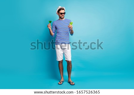Full body photo of funky traveler guy browsing telephone drink green cocktail all inclusive resort wear sun specs striped sailor shirt cap shorts flip flops isolated blue color background