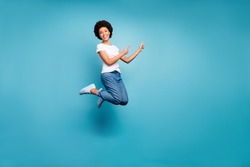 Full body photo of funny dark skin wavy lady jumping high directing fingers empty space offer black friday prices wear casual white t-shirt jeans isolated blue color background