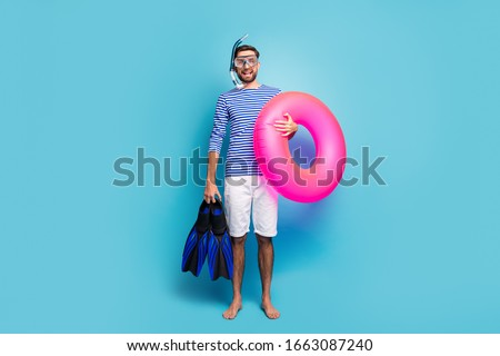 Full body photo of funny excited guy tourist swimmer hold underwater mask breathing tube flippers pink lifebuoy wear striped sailor shirt shorts isolated blue color background