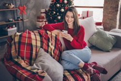Full body photo of girl sit couch read x-mas news on smartphone in house indoors with christmas advent decoration