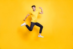 Full body photo of handsome guy jumping high waving arm old friends on streets glad to see them wear casual t-shirt black trousers isolated yellow color background