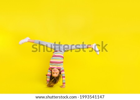 Full body photo of happy young pretty funky girl make handstand good mood isolated on yellow color background