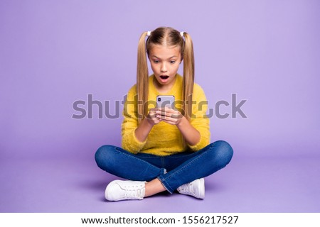 Full body photo of impressed child sit crossed folded legs use smartphone read social network notification scream omg wow wear yellow pullover sneakers isolated purple color background