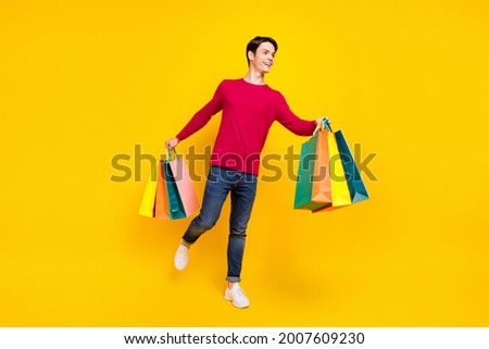 Full body photo of nice brunet young guy stand with bags look empty space wear red sweater jeans isolated on yellow color background Stock photo ©