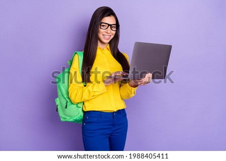 Full body photo of positive charming young woman hold laptop student education isolated on violet color background Foto stock ©
