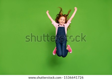 Full body photo of pretty little schoolchild jumping high rejoicing summer holidays hair flying warm wind wear casual denim overall pink shirt isolated green background