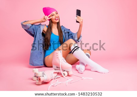Full body photo of pretty woman wearing cap blue bodysuit socks making photo v-signs isolated over pink background #1483210532