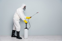 Full body photo of professional specialist guy disinfectant cleaning public transport during pandemic spraying surface wear white hazmat protective suit isolated grey color background