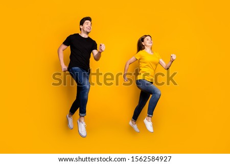 Full body photo of sporty guy lady couple jumping high active way of life pair race get to finish line first wear casual jeans black t-shirts isolated yellow color background