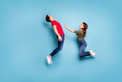 Full body photo of two married people strong woman kick man falling in knockout she winner in martial fight battle jump wear green red t-shirt denim jeans isolated blue color background