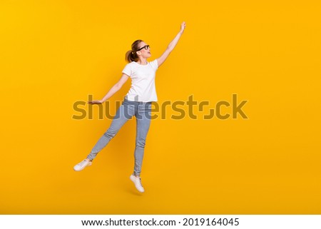 Full body photo of young attractive woman happy positive smile jump try to catch umbrella isolated over yellow color background Сток-фото ©