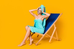 Full body photo of young woman sit chaise-longue enjoy facial treatment hands touch head isolated over yellow color background