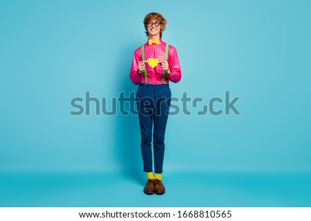 Full body photo positive nerd guy hold small yellow paper card heart show affectionate romantic love girlfriend wear pink green pants trousers socks shoes isolated blue color background ストックフォト ©