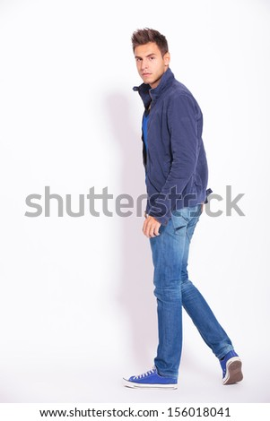full body picture of a casual man in jeans and jacket turning and looking at the camera, back view