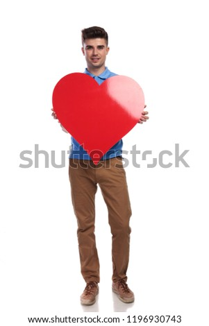full body picture of a young casual man holding a big red heart on white background #1196930743
