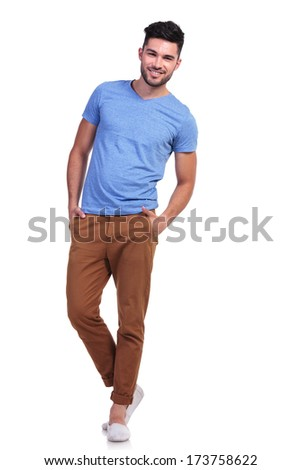 full body picture of a young casual man standing with hands in pockets and smiles #173758622