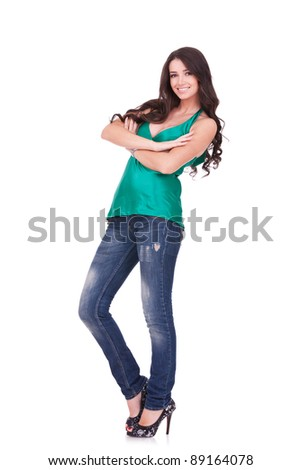 full body picture of a young casual woman standing with her arms crossed onwhite background
