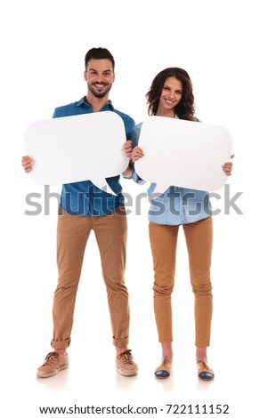 full body picture of casual couple smiling and holding speech bubbles on white background